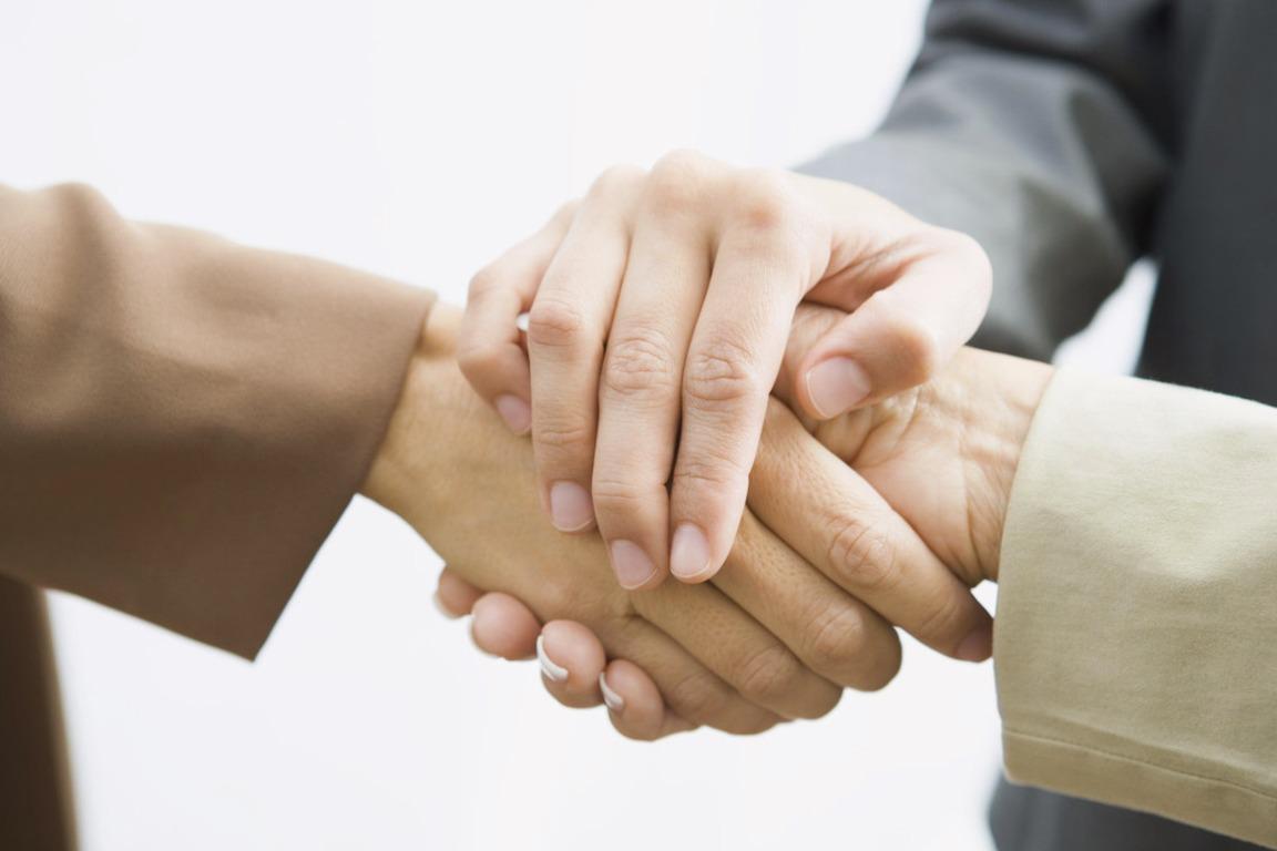 Dos personas dándose la mano y una encima